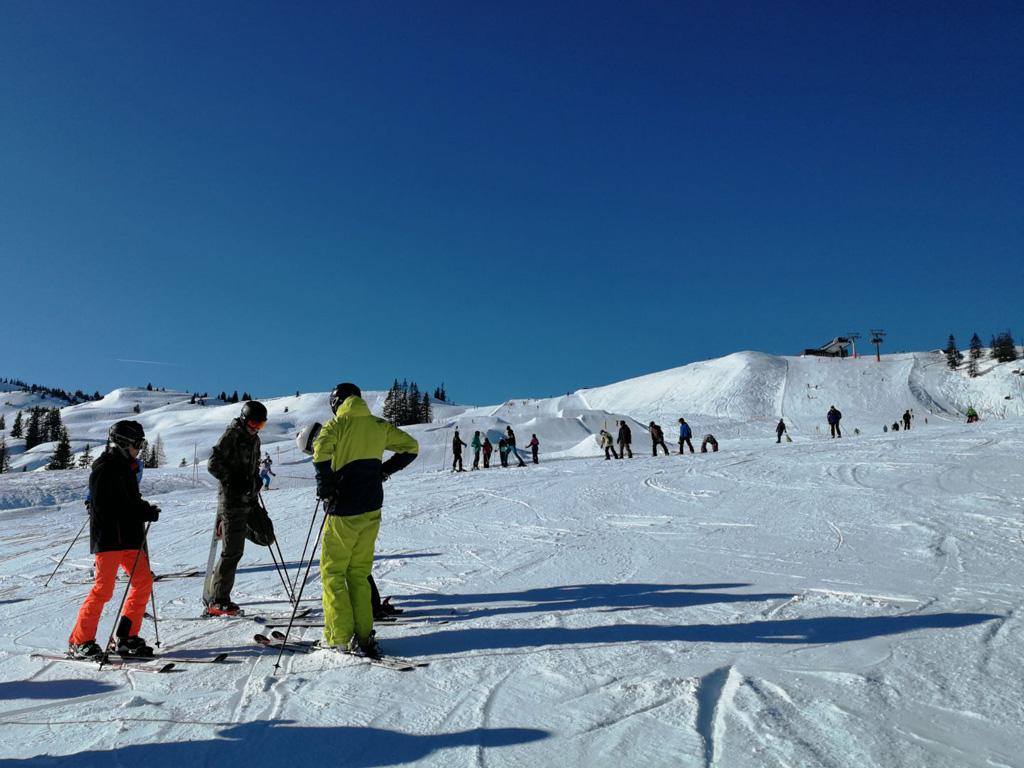 wintersporters op de piste in de zon