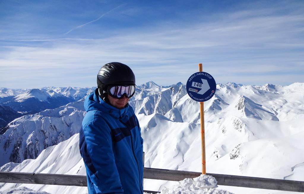 Skiër bij het pistebordje van de Arrez-Non-Stop