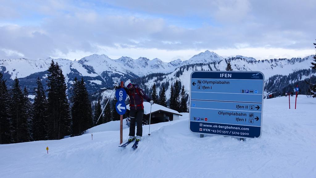 Skiër bij het bordje van een blauwe piste