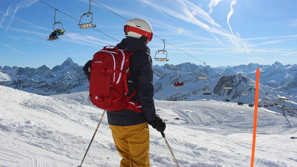 Wintersporter die stilstaat op de piste en geniet van het uitzicht