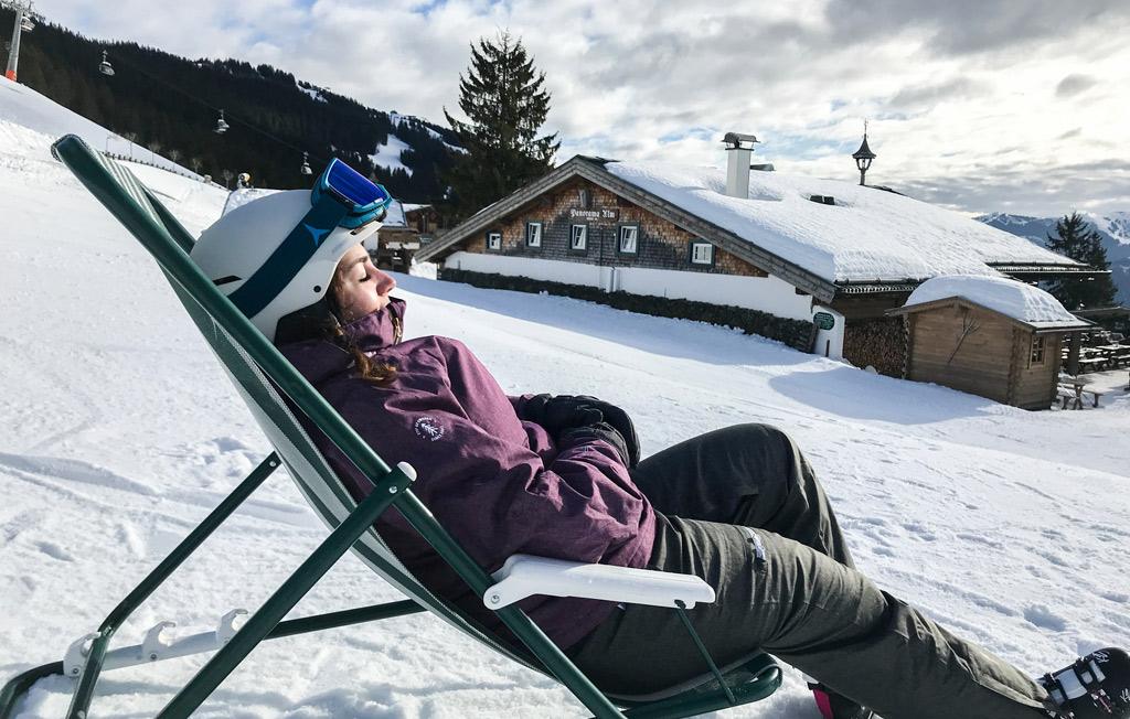Wintersporter in ligstoeltje op de piste in Saalbach