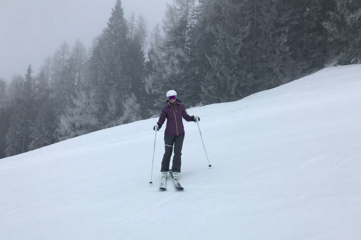 Skier on a slope below the tree line