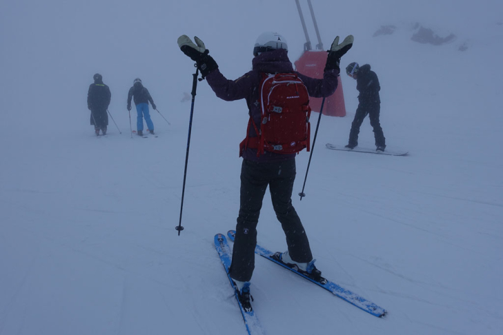 Group skiing in bad weather in the Alps