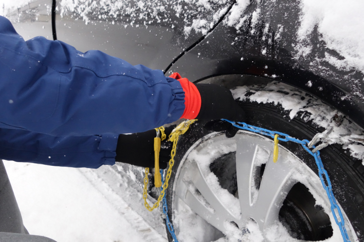 Putting on snow chains for a ski holiday