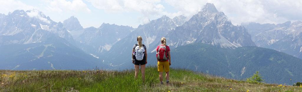 Twee vrouwen in het gras kijken naar de bergen aan de overkant