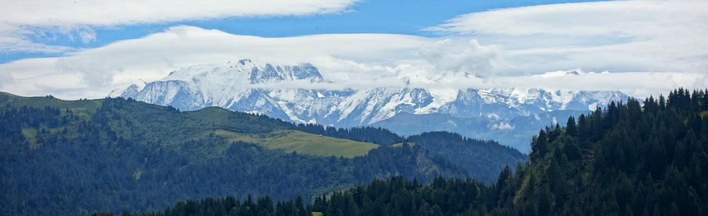 Groene heuvels en besneeuwde toppen van het Mont Blanc massief