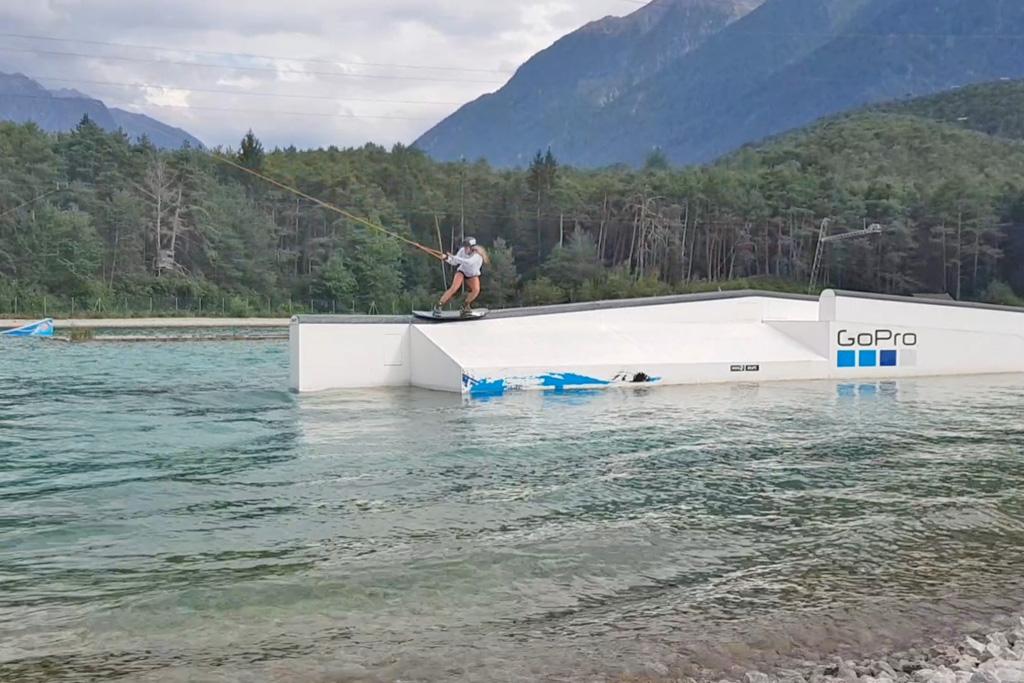 vrouw gaat over obstakel tijdens wakeboarden