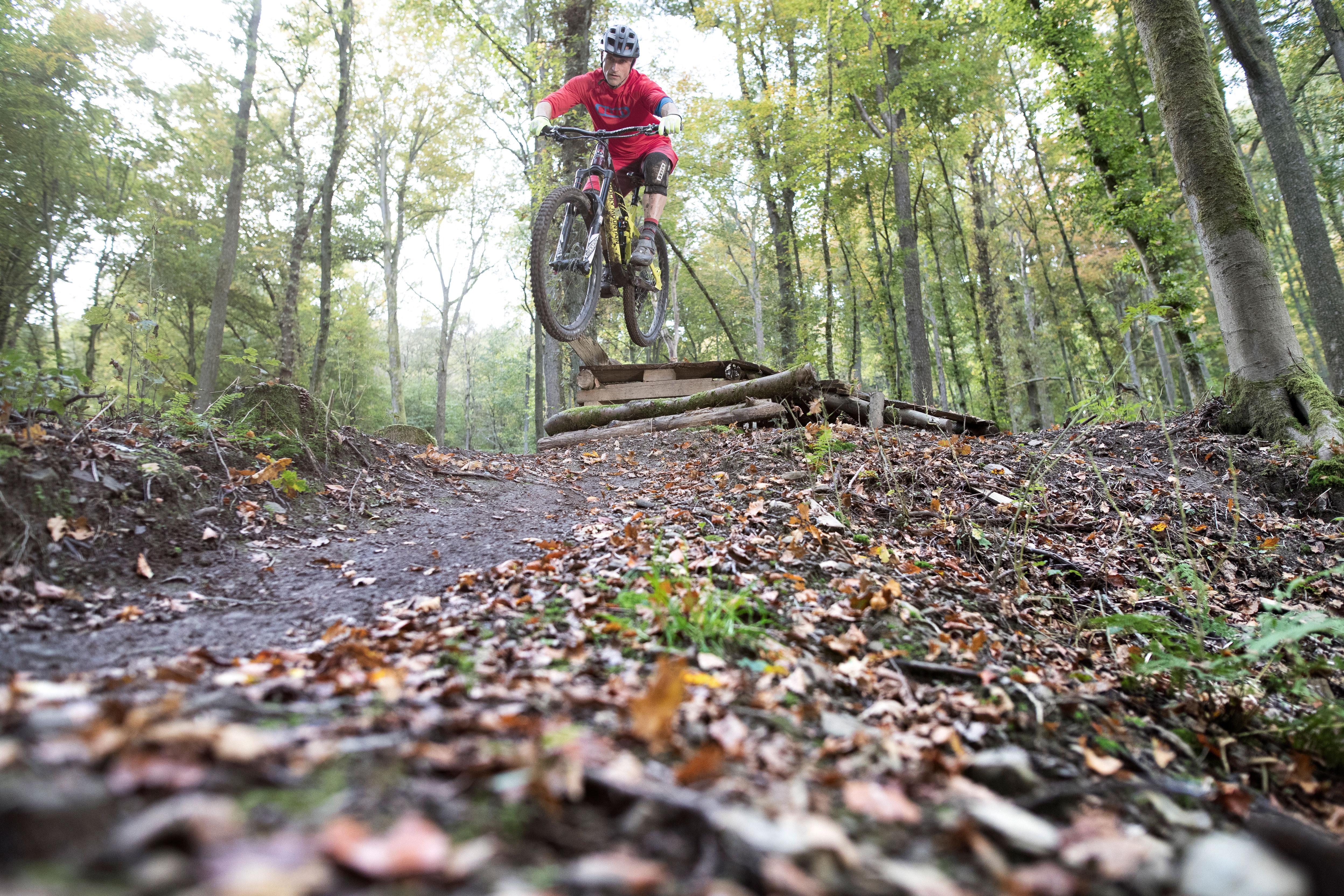 Mountainbiker springt in het bos bij Winterberg