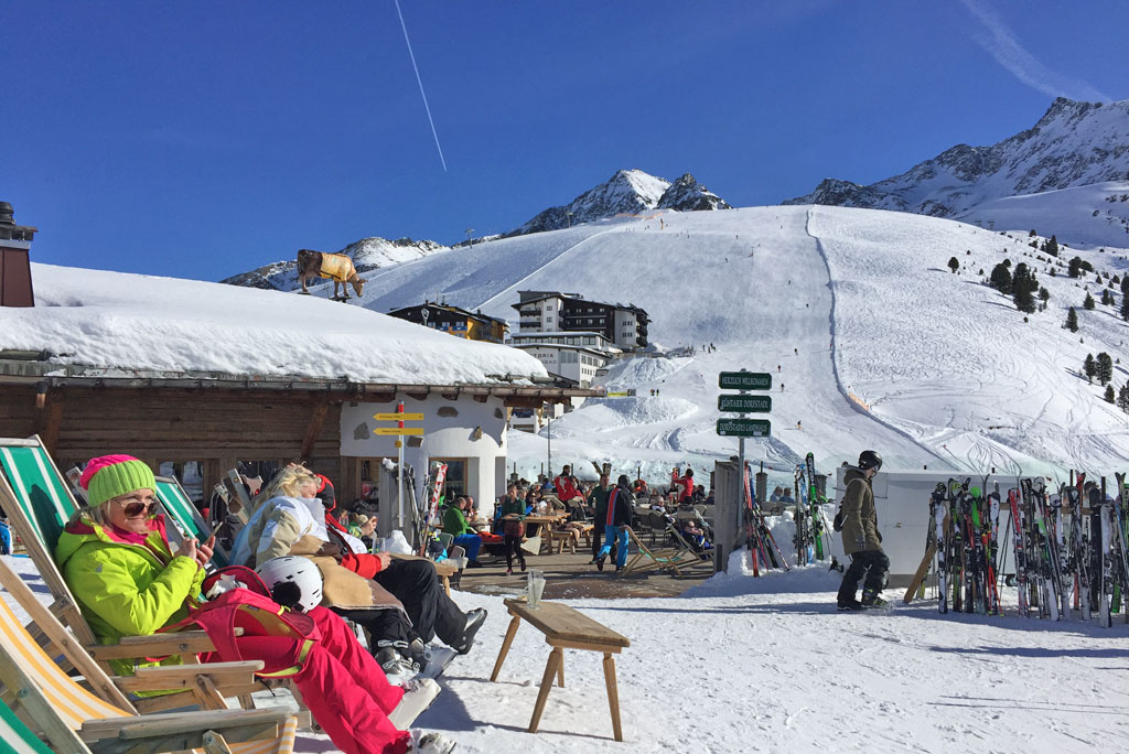 Sunny mountain terrace with skiers