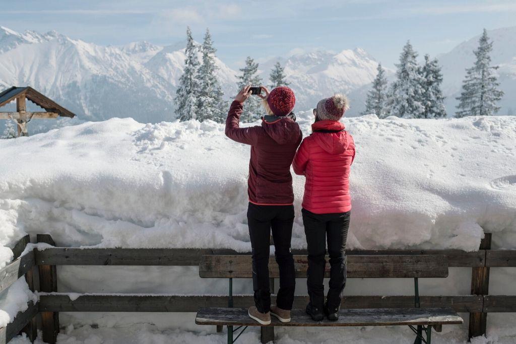 Zwei Wanderer stehen auf Bank fotografieren Winterlandschaft