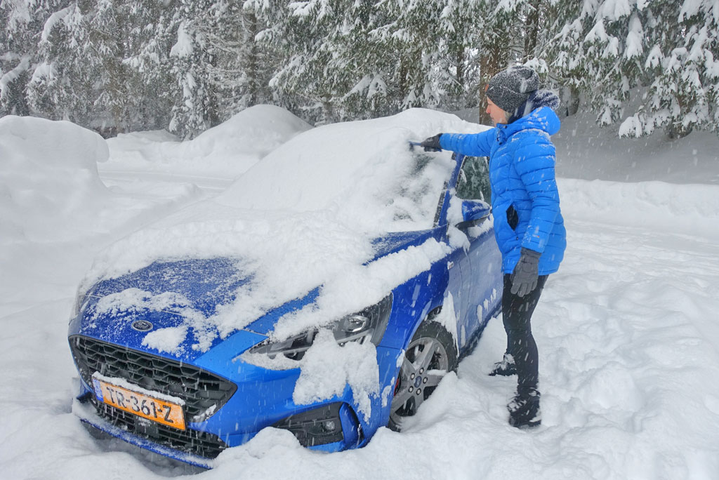 Scraping the snow off the car